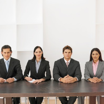 Front view portrait of four business executives sitting in a line